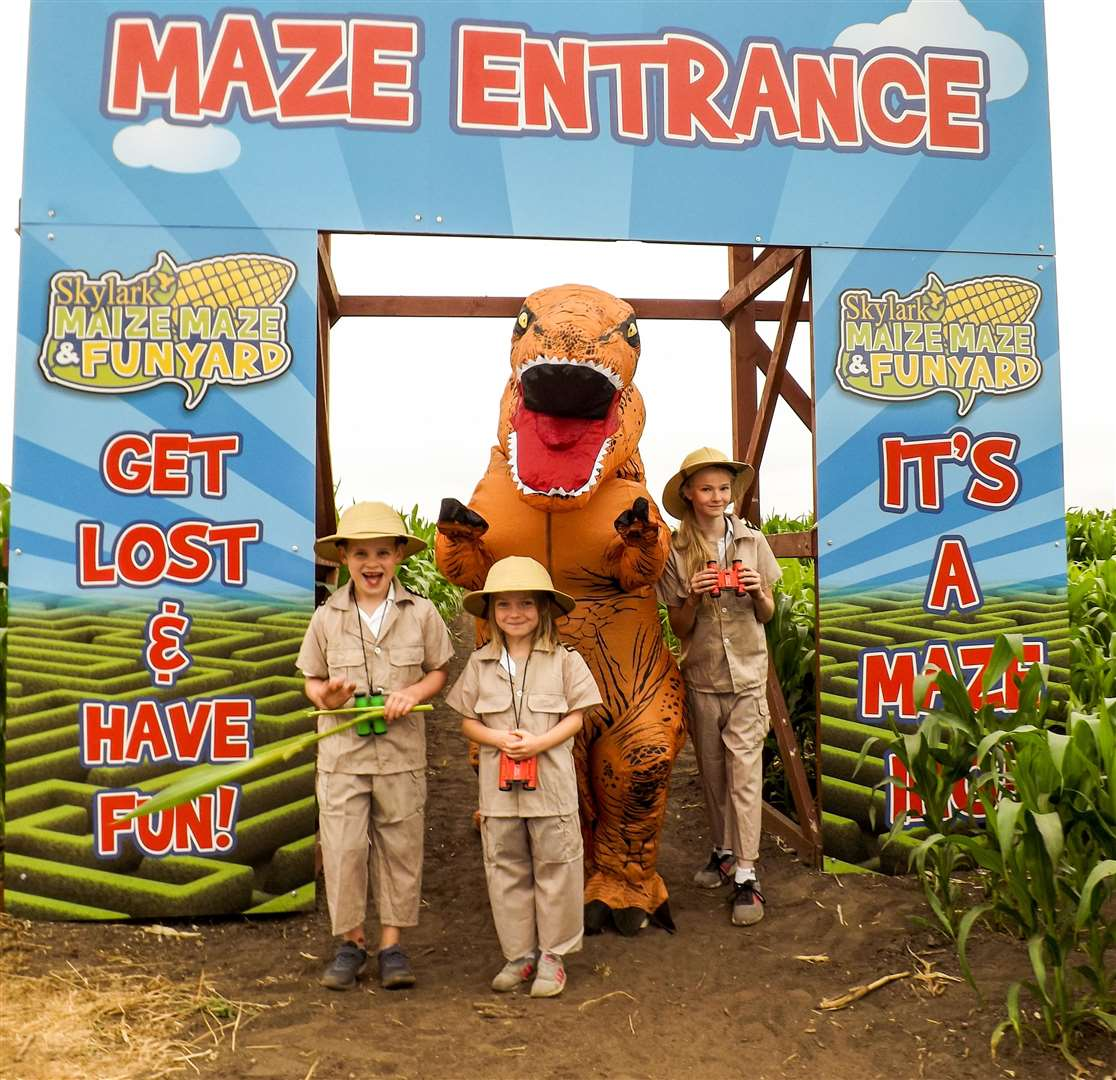 Owen Askew, 7, Amelia Hathaway, 6, and Annabell Wesley, 11, with the dinosaur at the entrance to the maize maze. (3047051)