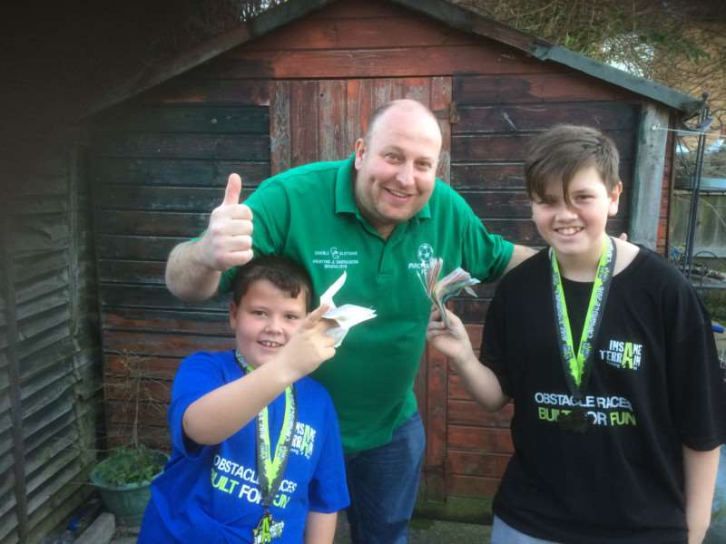 Owen, 12, and Jamie, 8, Burge with Macmillan FC manager Justin Cross.
