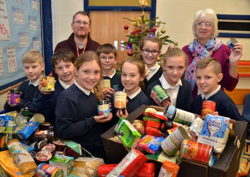 CAN-DO ATTITUDE: House captains at Long Sutton Primary School present the results of their Reverse Advent Calendar to Darren Fawcett and Irene Davies of Agapecare Foodbank. Photo by Tim Wilson. SG211216-107TW. ''ANL-161221-160607001