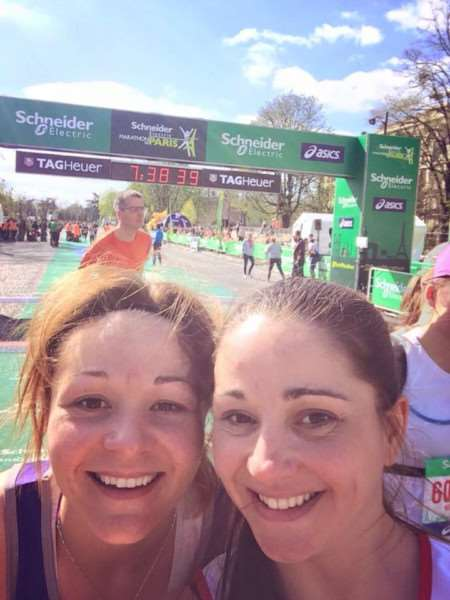 Stacey Rudd and Sallyanne Ellington cross the finish line of the Paris Marathon - their third marathon in 365 days to raise money for Cancer Research UK in memory of their dad.