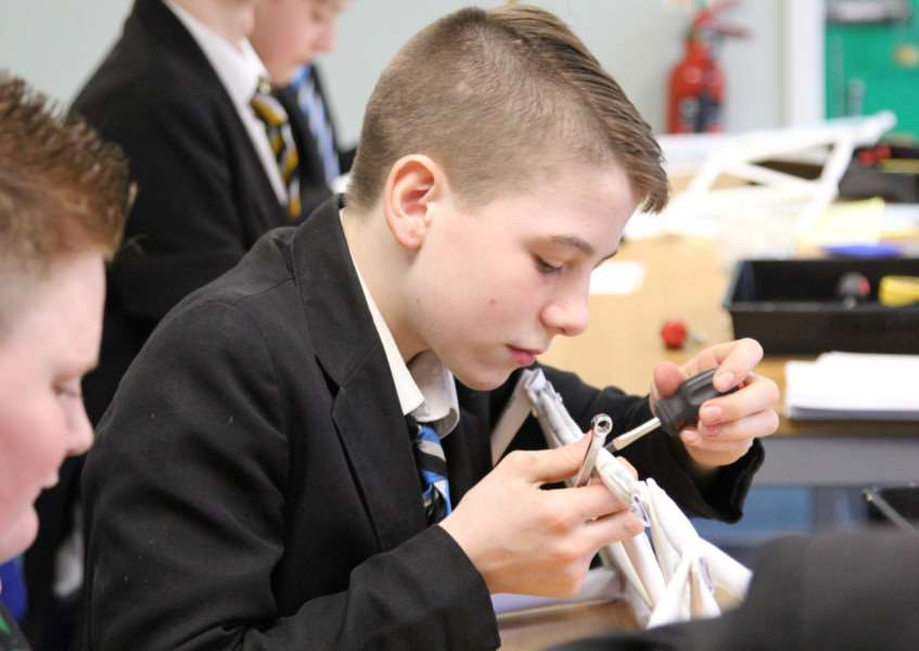 A student has a go at making a paper bridge during one of the Fenland Engineering Taster events.