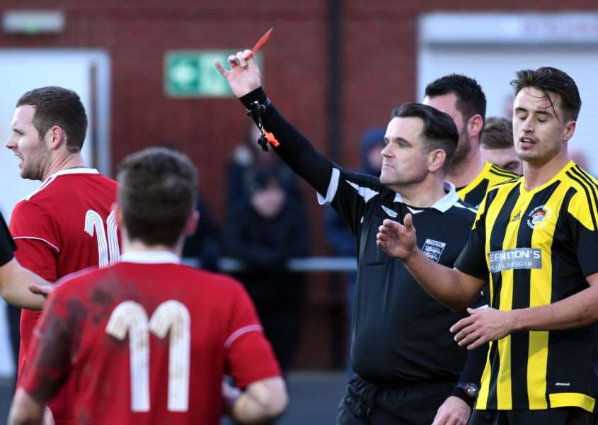 Referee Paul Dobbs shows the red card