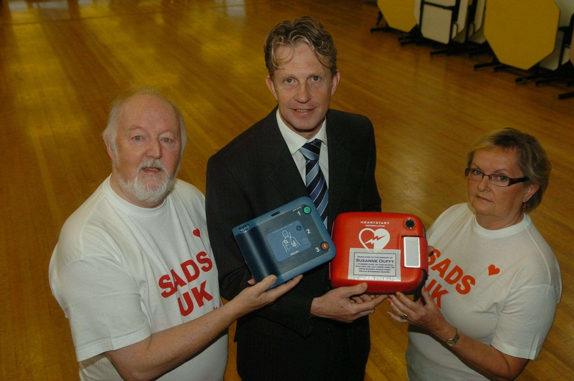 Ian Duffy (left) and wife Evelyn with Maathew Parr-Burman former headteacher of Marshland High School when they presented the school with a defibrillator in memory of Suzanne.