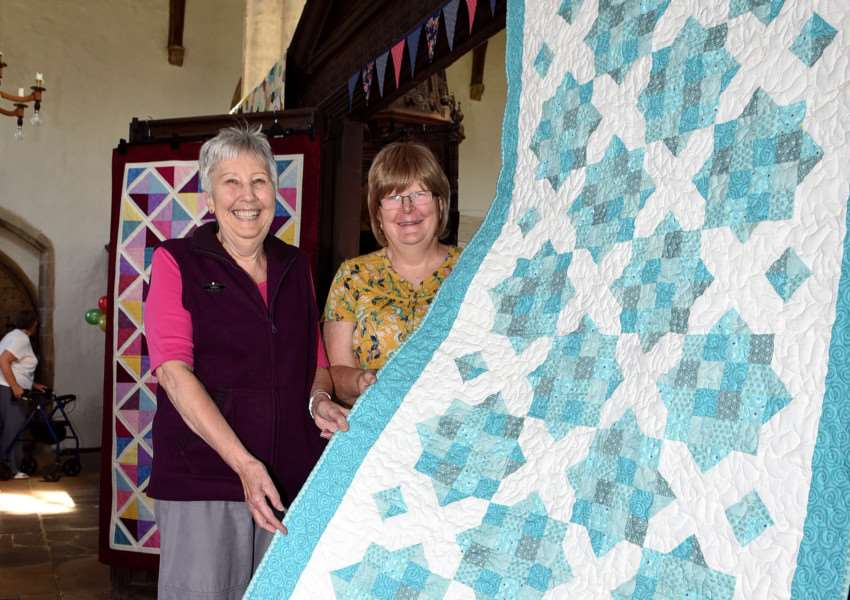 Gwen Ray and Gill Henderson show off one of the quilts during a craft and quilting display at Walpole St Peter Church.