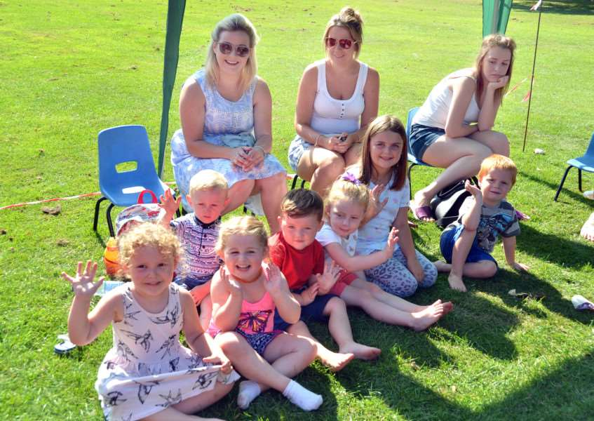 Youngsters and mums sit in the shade under a gazebo outside The Pavilion. Photo by Tim Wilson.