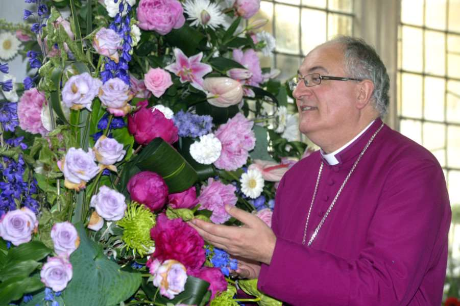 The Bishop of Ely, Bishop Stephen Conway, admires one of the arrangements at last year's Walpole St Peter Church flower festival.