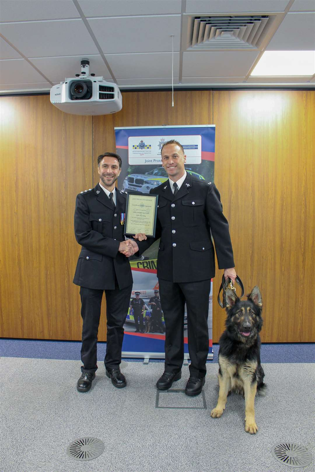 Chief Inspector Robin Sissons (left) awarding the certificate to Paul French and police dog Sonny (6158654)
