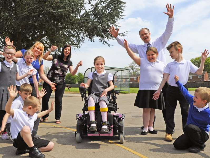 Sophie Clarke with her new wheelchair. Joining in the celebrations are class friends from Year 4, along with teaching assistant Nicki Payne (left), mum Mandy Seaton, and headteacher Andrew Saunders.
