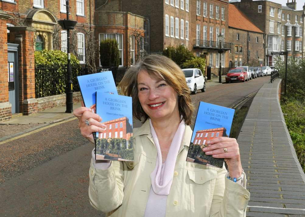 With a backdrop of North Brink, Wisbech, author Diane Smith with her new book. ANL-150413-132858009